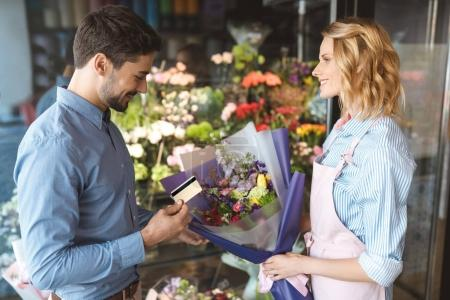 Photo for Side view of smiling man with credit card and young florist with bouquet in flower shop - Royalty Free Image