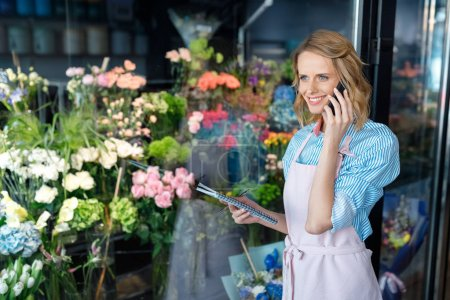 Photo for Smiling young florist talking on smartphone while holding notebook in flower shop - Royalty Free Image