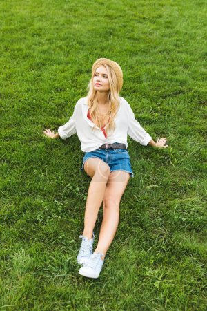 Photo for Thoughtful beautiful woman in straw hat looking away while resting on green lawn in park - Royalty Free Image