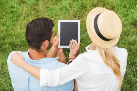 couple with tablet on green lawn