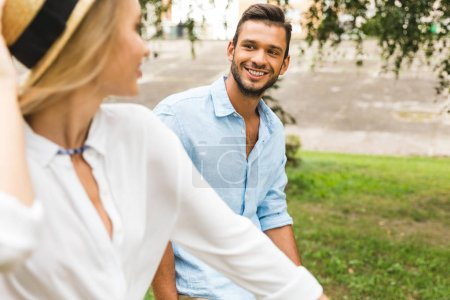 Photo for Selective focus of smiling man looking at girlfriend in park - Royalty Free Image