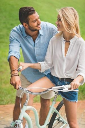 Photo for Portrait of smiling couple with bicycle looking at each other in park - Royalty Free Image