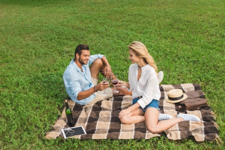 Photo pour Verres de tintements heureux couple de vin rouge sur rendez-vous romantique dans le parc - image libre de droit