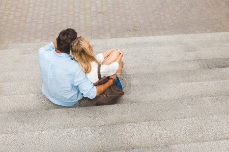 Couple sitting on stairs on street