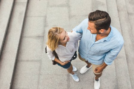 Photo for Overhead view of man and woman hugging and looking at each other on street - Royalty Free Image
