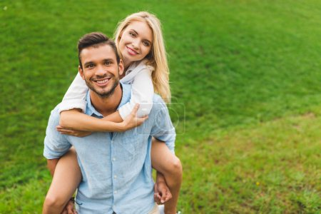 Photo for Happy man and woman looking at camera while piggybacking together on green lawn - Royalty Free Image