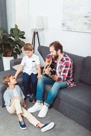 Foto de Feliz padre tocar la guitarra a lindos hijos pequeños en casa - Imagen libre de derechos