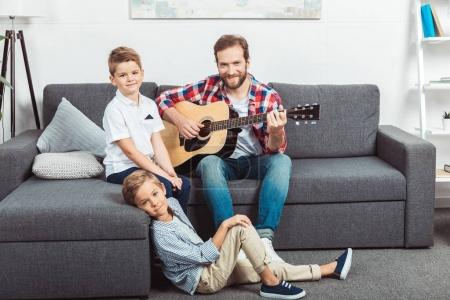 father with sons playing guitar