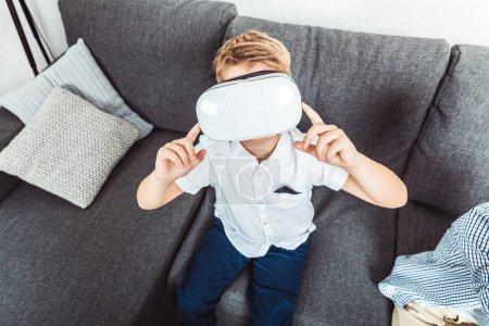 Photo pour Vue de la forte inclinaison du petit garçon assis sur le canapé à la maison à l'aide de casque de réalité virtuelle - image libre de droit
