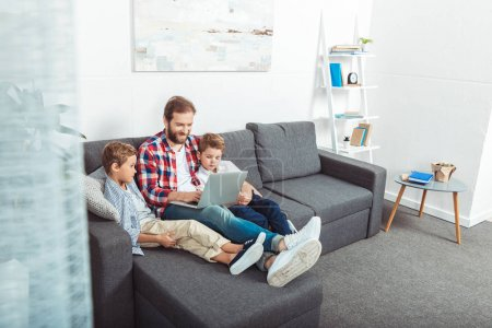 Photo for Happy father with cute little sons using laptop together at home - Royalty Free Image