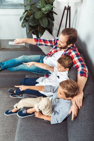 father with sons watching tv