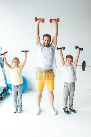 father and sons exercising with dumbbells