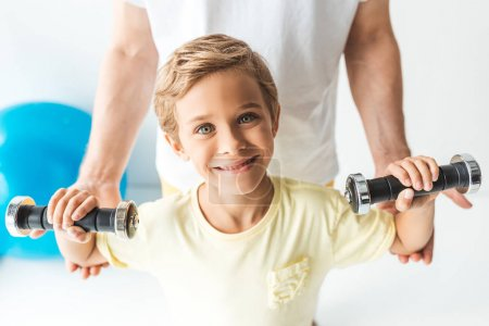 father and son training with dumbbells