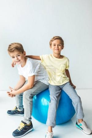 boys sitting on fitness ball
