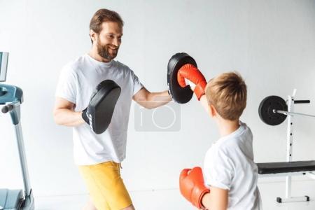 Photo pour Heureux père et mignon petit fils boxe ensemble dans la salle de gym - image libre de droit