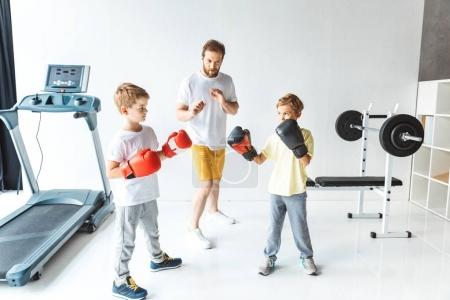 trainer and boys in boxing gloves