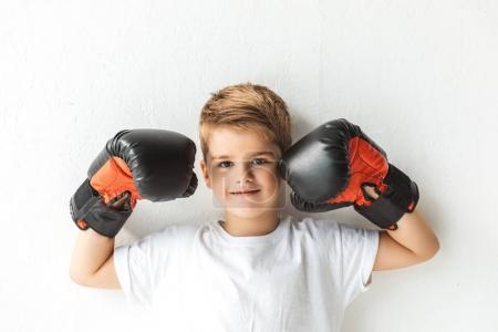 Photo pour Adorable petit garçon en souriant à la caméra sur le blanc des gants de boxe - image libre de droit