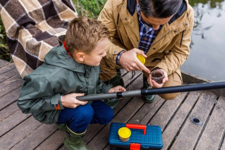 Photo for Father and son with fishing rod on wooden pier at lake - Royalty Free Image