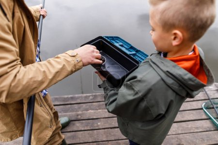 Father and son fishing on pier
