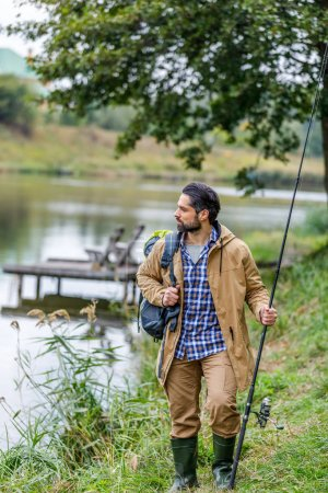 Fisherman with rod and backpack