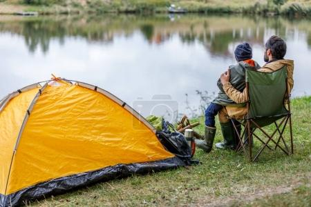father and son sitting at tent