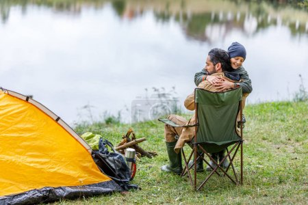 Photo for Happy father and son hugging in camping with tent at lake - Royalty Free Image