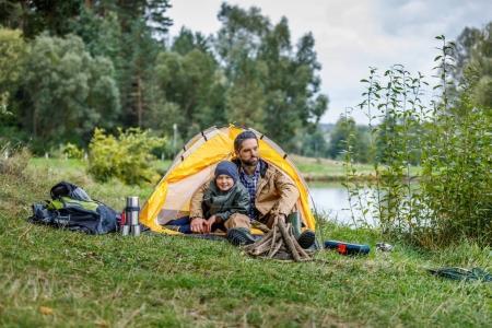Photo pour Père et fils assis dans le camping avec tente au lac - image libre de droit