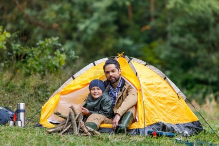 Photo for Happy father and son sitting in tent in forest camping - Royalty Free Image