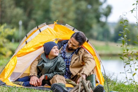 Photo for Happy father and son sitting in tent in camping at countryside - Royalty Free Image