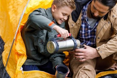 Photo for Happy son pouring hot drink from thermos to fathers cup white sitting in camping tent - Royalty Free Image