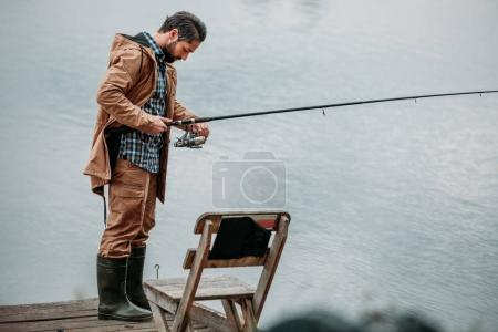Man fishing with rod on pier
