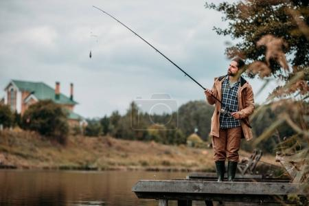 man fishing with rod at lake