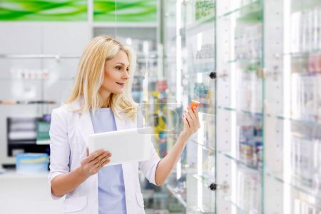 Photo for Smiling female pharmacist in white coat holding digital tablet and medication - Royalty Free Image