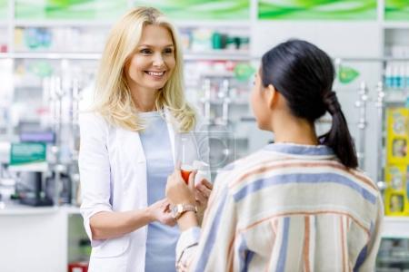 Photo for Smiling female pharmacist giving containers with pills to customer in drugstore - Royalty Free Image