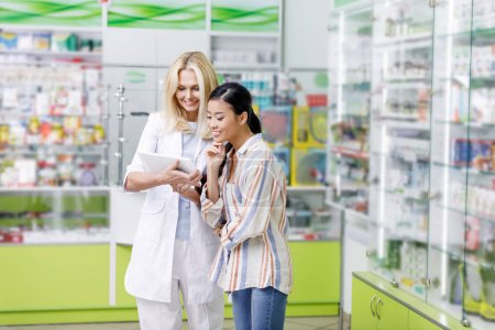 pharmacist with digital tablet and customer