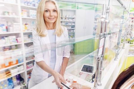 Photo for Female pharmacist smiling at camera while taking credit card from customer in drugstore - Royalty Free Image