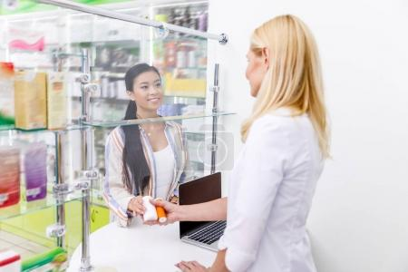 Photo for Pharmacist and customer holding containers with pills  in drugstore - Royalty Free Image