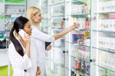Pharmacists with devices in drugstore