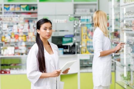 Foto de Mujer asiática farmacéutico con tableta digital mirando a cámara en droguería - Imagen libre de derechos