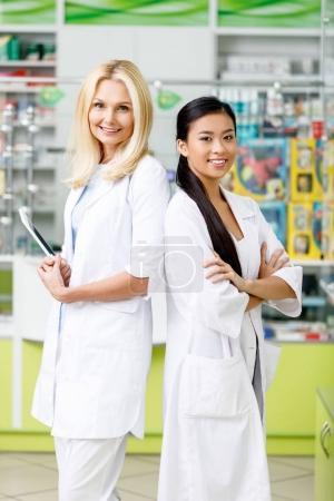 Photo pour Pharmaciens multiethniques avec tablette numérique debout avec bras croisés et souriant à la caméra en pharmacie - image libre de droit