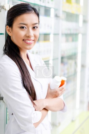 Photo for Young asian pharmacist holding containers with medication and smiling at camera - Royalty Free Image