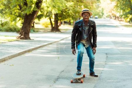Foto de Afro americano hombre de sombrero de paja sobre un longboard en el parque de patinaje - Imagen libre de derechos