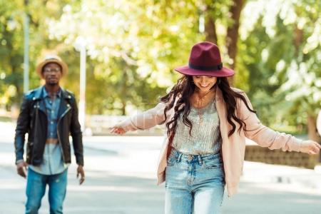 Photo pour Petit ami en regardant sa petite amie dans un parc de planche à roulettes - image libre de droit
