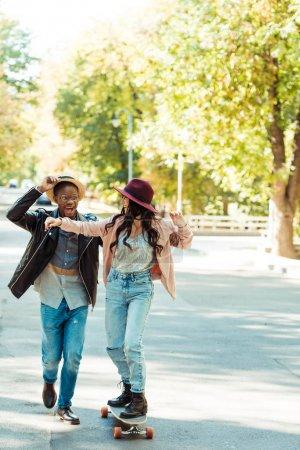 Photo pour Petit ami dans le chapeau de paille aider son amie à patiner sur un longboard dans le parc - image libre de droit