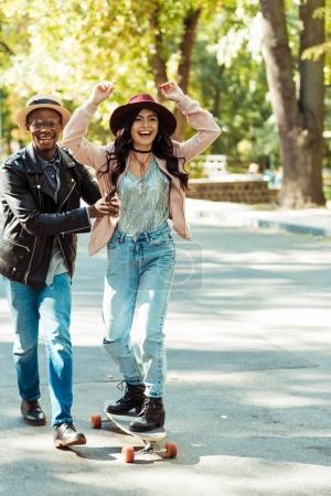 Boyfriend helping girlfriend skate on longboard
