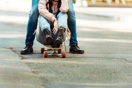 Girlfriend sitting on longboard