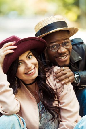 smiling multicultural couple in hats