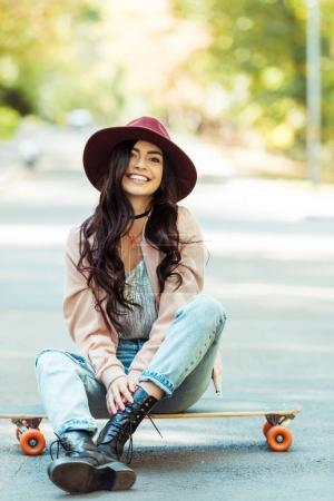 Smiling woman sitting on longboard