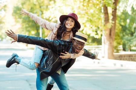 Photo for Boyfriend in straw hat giving piggyback to his girlfriend while walking in the park - Royalty Free Image