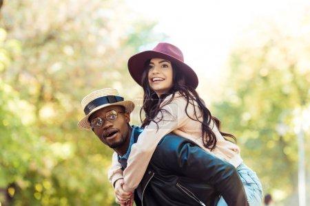 Foto de Novio que piggyback a su novia mientras caminaba en el Parque - Imagen libre de derechos